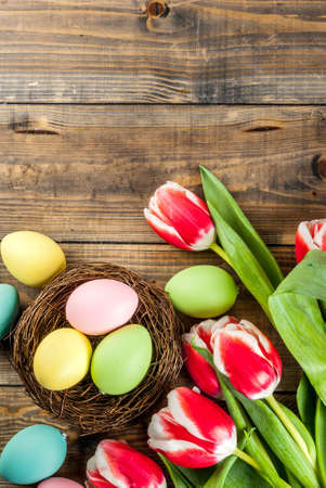Multicolored Easter eggs with tulips flowers on wooden background,copy space top view