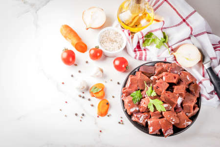 Sliced raw beef liver with spices, herbs and vegetables, white marble table copy space top view Stock Photo