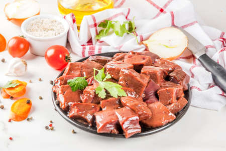 Sliced raw beef liver with spices, herbs and vegetables, white marble table copy space Stock Photo