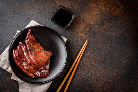 Asian cuisine, delicacies. Raw beef liver with teriyaki sauce and black sesame, dark rusty  table copy space top view Stock Photo