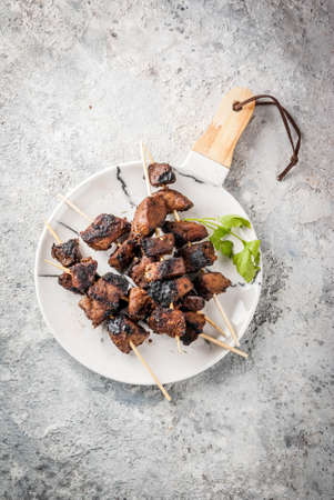 Grilled beef liver on skewers, with teriyaki or soy sauce, yakitori, grey stone table copy space top view