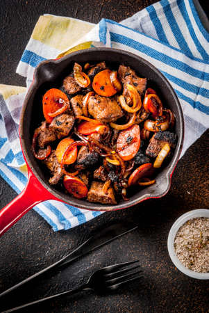 Roasted or grilled beef liver with onion and carrot in portioned frying pan, dark rusty  table copy space top view Stock Photo