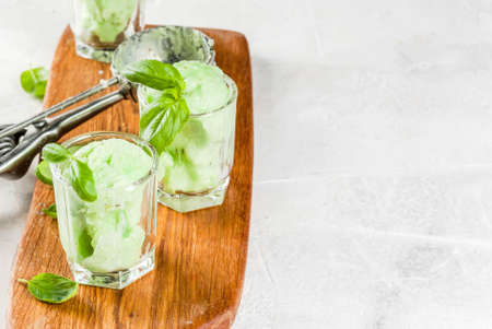 Summer desserts. Vegan food. Basil ice cream in serving glasses, decorated with fresh basil leaves. On a wooden cutting board, on a stone white table. Copy space Stock Photo