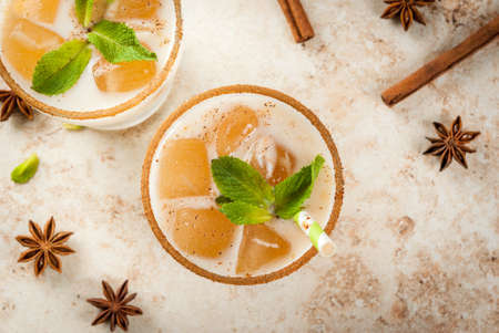 Traditional Indian drink is iced tea or chai masala, with ice cubes from chai, milk and mint leaves. With striped straws. On light beige stone table. Copy space top view