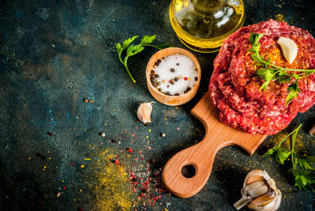 Raw burger cutlets with salt, pepper, oil, herbs and spice, on dark table, copy space top view