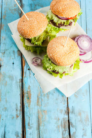 Picnic, Fast food. Unhealthy food. Delicious Fresh Tasty Burgers with Beef Cutlet, fresh Vegetables and Cheese on old rustic blue wooden table with sweet soda water. Copy space  top view