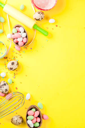 Sweet baking concept for Easter, cooking background with baking - with a rolling pin, whisk for whipping, cookie cutters, quail eggs, sugar sprinkling. Bright yellow background, copy space top view