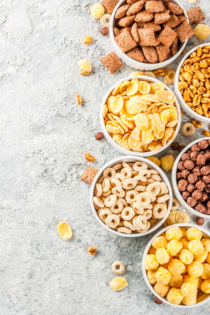 Set of various breakfast cereal corn flakes, puffs, pops, grey stone table copy space top view Stock Photo