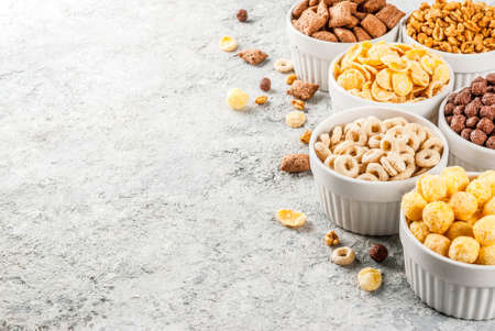 Set of various breakfast cereal corn flakes, puffs, pops, grey stone table copy space