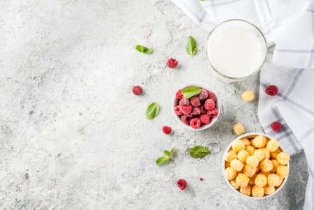 Healthy breakfast ingredients. Breakfast cereal, milk or yogurt glass, raspberries and mint on grey stone background, copy space top view Stock Photo