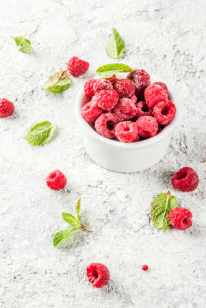 Fresh raspberries with mint in small bowl, on grey stone background, copy space Stock Photo
