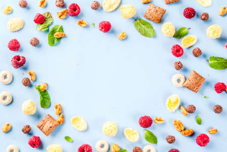 Healthy breakfast ingredients concept. Various breakfast cereal, raspberries and mint on blue background, copy space top view frame Stock Photo