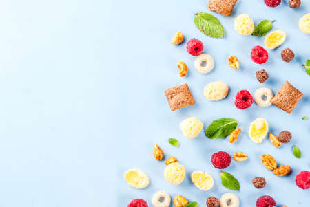 Healthy breakfast ingredients concept. Various breakfast cereal, raspberries and mint on blue background, copy space top view Stock Photo