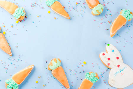 Easter holiday concept, sweet cookies in form of carrots, Easter bunny, with sweet sprinkles, light blue background copy space top view, greeting card background