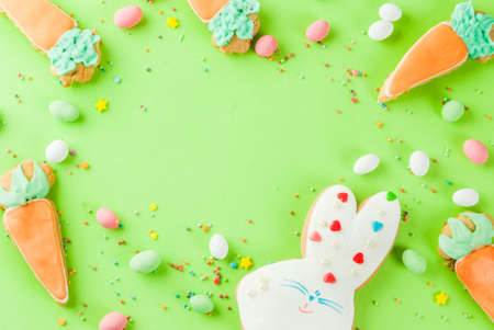 Easter holiday concept, sweet cookies in form of carrots, Easter bunny, with sweet sprinkles and egg candies, light green background copy space top view, greeting card background