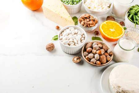 Healthy food concept. Set of food rich in calcium - dairy and vegan Ca products, white marble background copy space