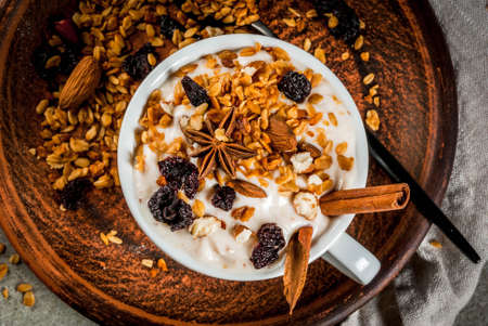 Ideas for an autumn winter breakfast. Spicy yoghurt with granola, dried berries, nuts, almonds, spices (cinnamon, anise), in cup, on plate. Gray background, close top view