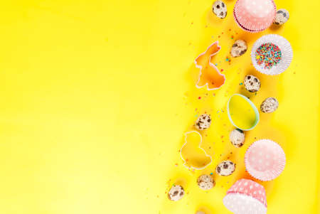 Sweet baking concept for Easter, cooking background with baking - with a rolling pin, whisk for whipping, cookie cutters, quail eggs, sugar sprinkling. Bright yellow background, top view copy space
