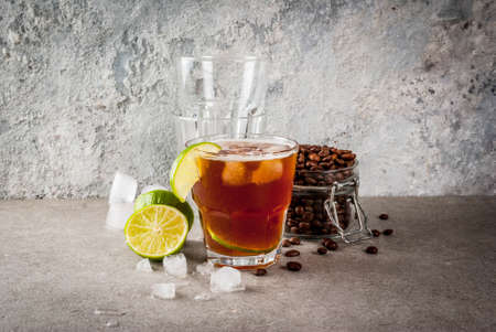 Espresso Tonic, refreshment summer drink with tonic water, lime and coffee, grey stone table, copy space