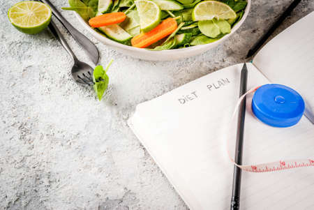Diet plan weight lose concept, fresh vegetable salad with fork, knife, note pad,  grey stone table copy space Stock Photo