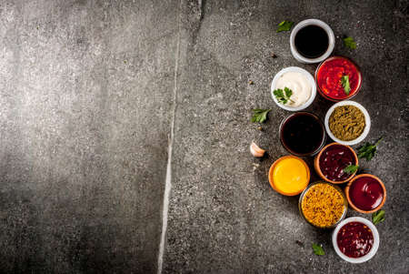 Set of different sauces - ketchup, mayonnaise, barbecue, soy, teriyaki, mustard, grain hills, pesto, adzhika, chutney, tkemali, pomegranate sauce on black stone background. Copy space top view
