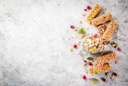 Healthy breakfast and snack concept, homemade granola with fresh raspberries in jar and nuts and granola bars, on grey stone stone background copy space top view Stock Photo