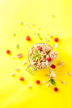 Healthy breakfast and snack concept, homemade granola with fresh raspberries in jar, on bright yellow background copy space  top view Stock Photo