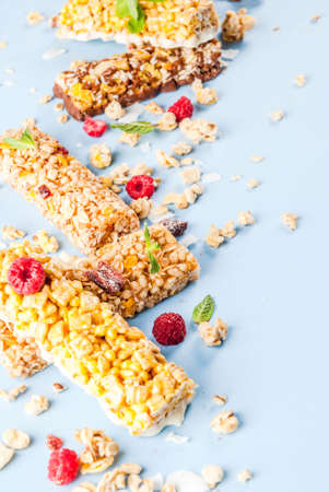 Healthy breakfast and snack concept, homemade granola with fresh raspberries and nuts and granola bars, on bright blue background copy space  Stock Photo