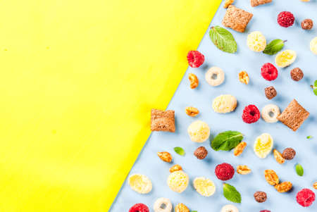 Healthy breakfast ingredients concept. Various breakfast cereal, raspberries and mint on blue yellow background, copy space top view Stock Photo