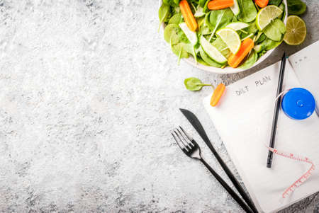 Diet plan weight lose concept, fresh vegetable salad with fork, knife, note pad,  grey stone table copy space top view Foto de archivo
