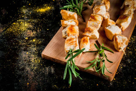Grill, barbecue meat. Chicken skewers with rosemary. On a black rusty metallic background, copy space