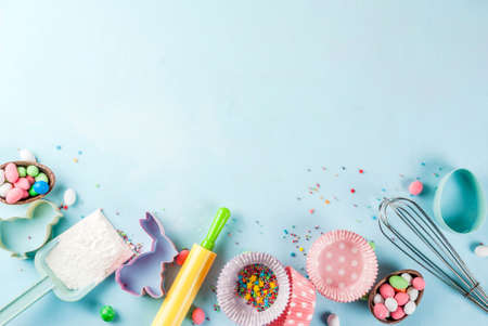 Sweet baking concept for Easter,  cooking background with baking - with a rolling pin, whisk for whipping, cookie cutters, sugar sprinkling, flour. Light blue background, top view copy space