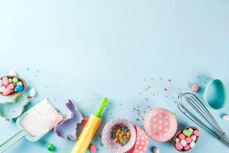 Słodka koncepcja wypieku na Wielkanoc, tło z pieczeniem - wałkiem do ciasta, trzepaczka do ubijania, foremki do ciastek, posypanie cukrem, mąka. Jasnoniebieskie tło, widok z góry kopia przestrzeń