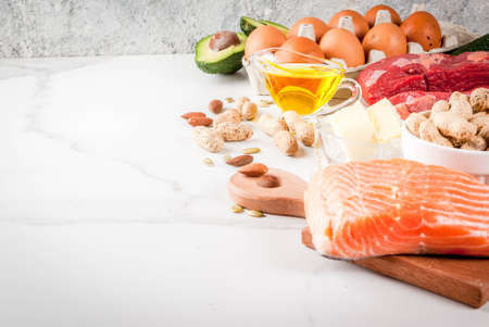 Ketogenic low carbs diet concept. Healthy balanced food with high content of healthy fats. Diet for the heart and blood vessels. Organic food ingredients, white marble background, copy space top view