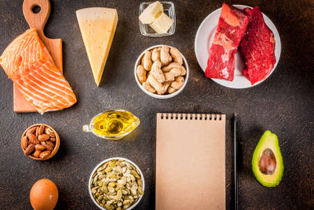 Ketogenic low carbs diet concept. Healthy balanced food with high content of healthy fats. Diet for the heart, vessels. Organic ingredients, dark rusty background, copy space top view with notepad Banque d'images