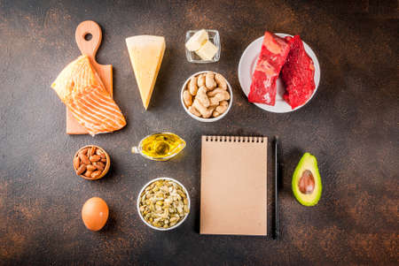 Ketogenic low carbs diet concept. Healthy balanced food with high content of healthy fats. Diet for the heart, vessels. Organic ingredients, dark rusty background, copy space top view with notepad Stock Photo