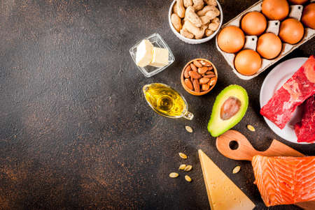 Ketogenic low carbs diet concept. Healthy balanced food with high content of healthy fats. Diet for the heart and blood vessels. Organic ingredients, dark rusty background, copy space top view