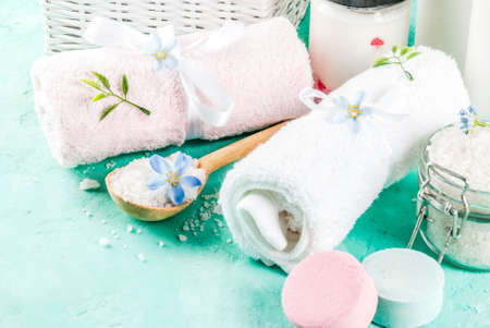 Spa relax and bath concept, sea salt, soap, with cosmetics and towels on light blue conrete background, copy space Stock Photo