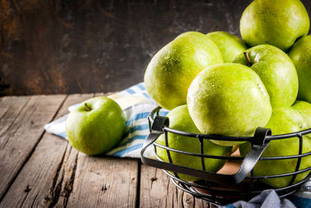 Fresh raw organic farm green apples in black metal basket, old rustic wooden background, copy space Stockfoto