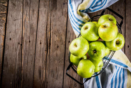 Fresh raw organic farm green apples in black metal basket, old rustic wooden background, copy space top view