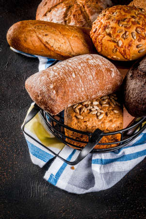 Variety of fresh homemade grain bread, in a metal basket, dark rusty background copy space
