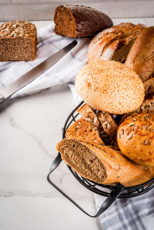 Variety of fresh homemade grain bread, in a metal basket, white marble background copy space