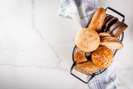 Variety of fresh homemade grain bread, in a metal basket, white marble background copy space top view