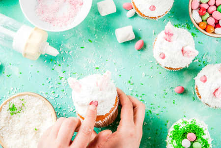 Making easter cupcakes, person decorate cakes with bunny ears and candy eggs, copy space frame top view, girls hands in picture