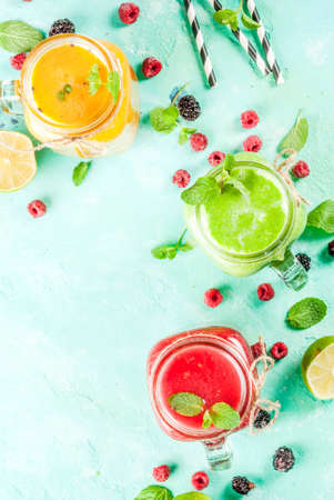 Healthy fresh fruit and veggie smoothies with ingredients on light blue concrete table, copy space top view Stockfoto