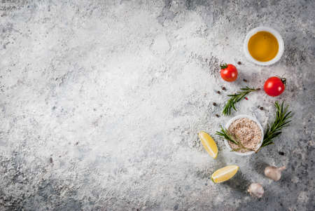 Food cooking ingredient, olive oil, herbs and spices, grey stone background top view copy space