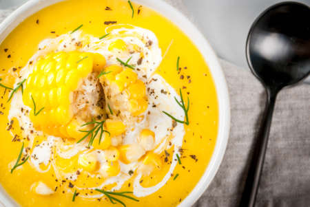 Vegan cuisine. Traditional autumn corn soup. Served with corn cobs, greens, cream. On a white marble table. Close top view