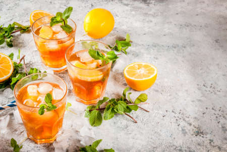 Cold summer drink. iced tea with lemon and mint, on grey stone background.  Copy space Stockfoto
