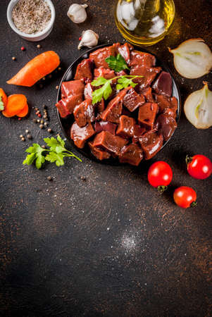 Sliced raw beef liver with spices, herbs and vegetables, dark rusty table copy space top view
