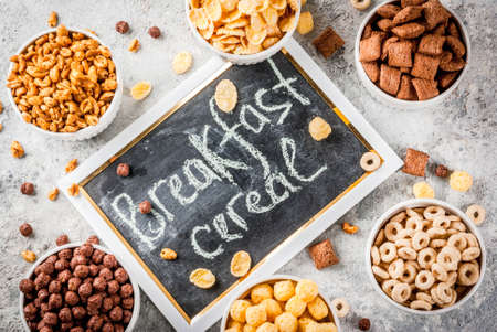 Set of various breakfast cereal corn flakes, puffs, pops, grey stone table copy space top view Stockfoto